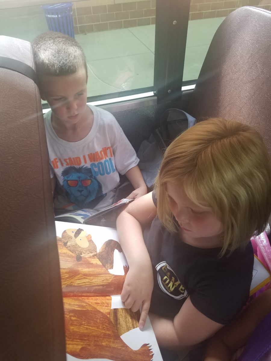 Students reading a book on the bus