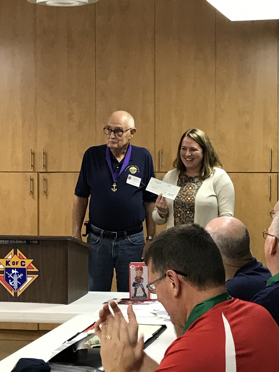 Megan Rivet accepting check for special needs students from the Knights of Columbus