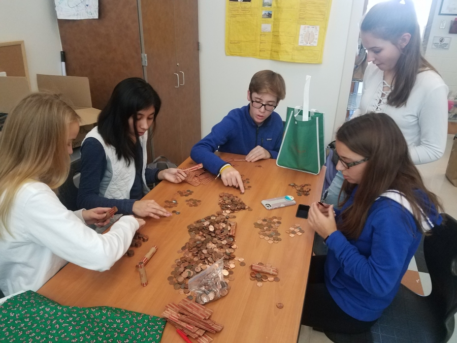 students counting money from the change for change day to raise money for the BLOC house.